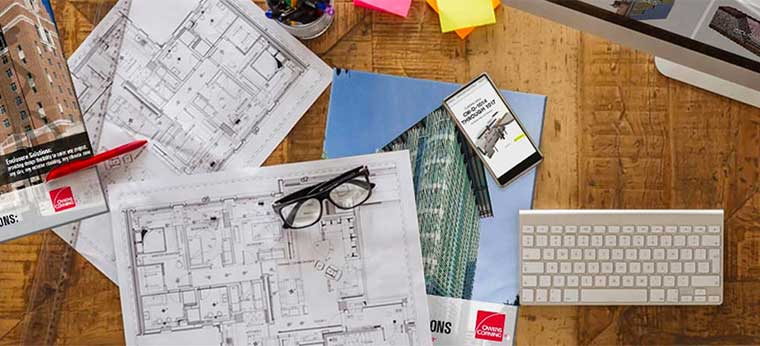 Blueprints and brochures on desk. Considering how Owens Corning products can work with your building project.